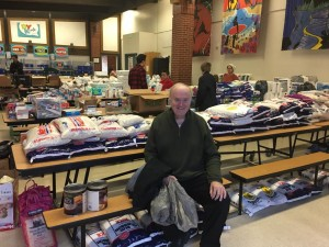 Don Ward, center, sits in front of donations for refugees collected at a Granite Park Junior High School parent teacher conference. Ward, now 75 years old, has dedicated his life to serving refugees since surviving a battle with cancer about eight years ago. (Stacey Gheen James via Facebook)