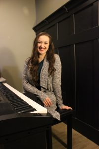 Rebecca Soelberg sits at a piano in a vocal studio where she teaches voice lessons