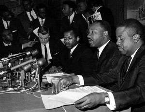 In this April 2, 1965 file photo, Dr. Martin Luther King Jr., second from right, speaks at a news conference next to John Lewis, to his left, chairman of the Student Nonviolent Coordinating Committee, in Baltimore. Rev. Dr. Joan Brown Campbell invited King to speak at the entirely white church congregation during the Civil Rights era.