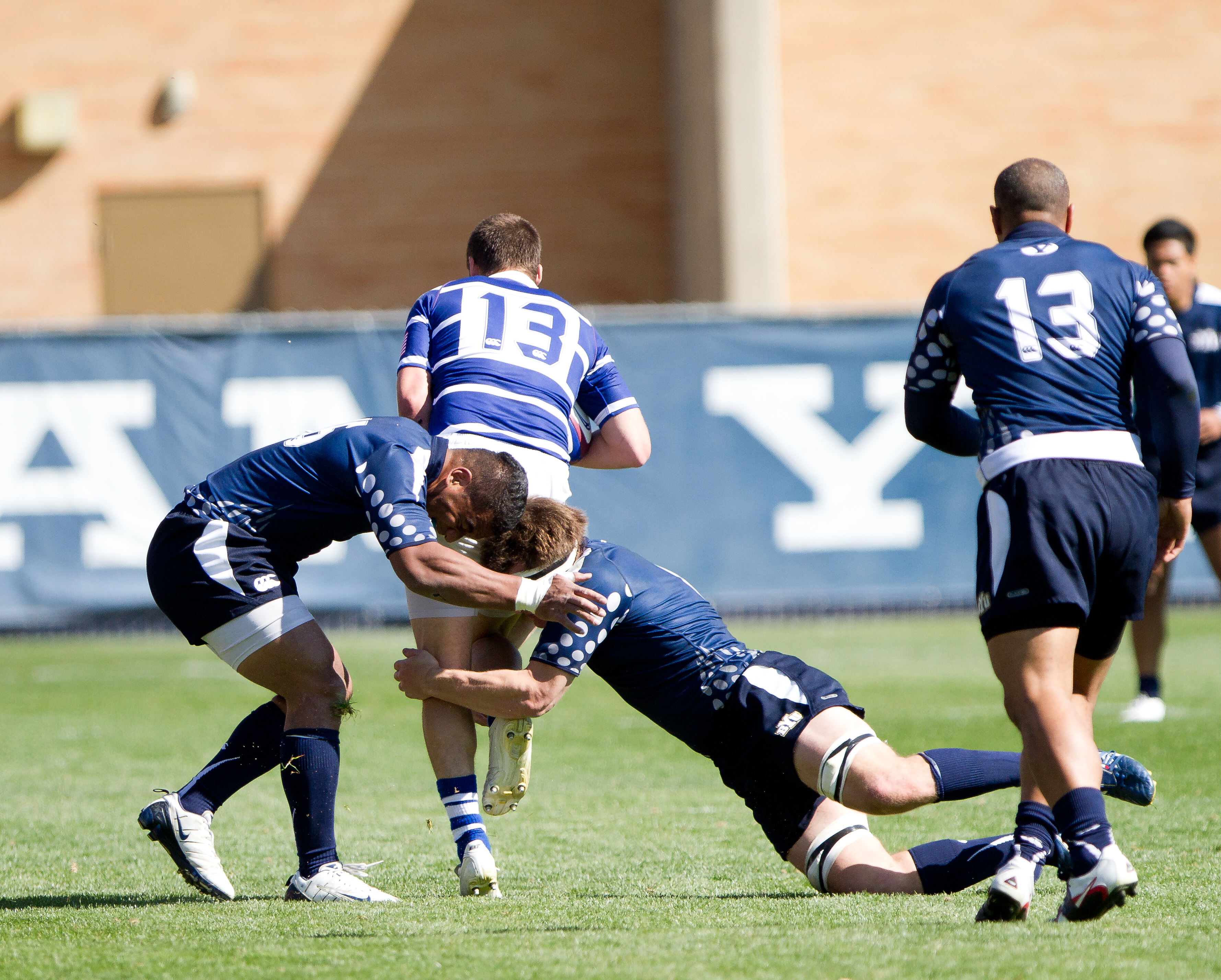 Two BYU players take down an Airforce player during a game at South Field.