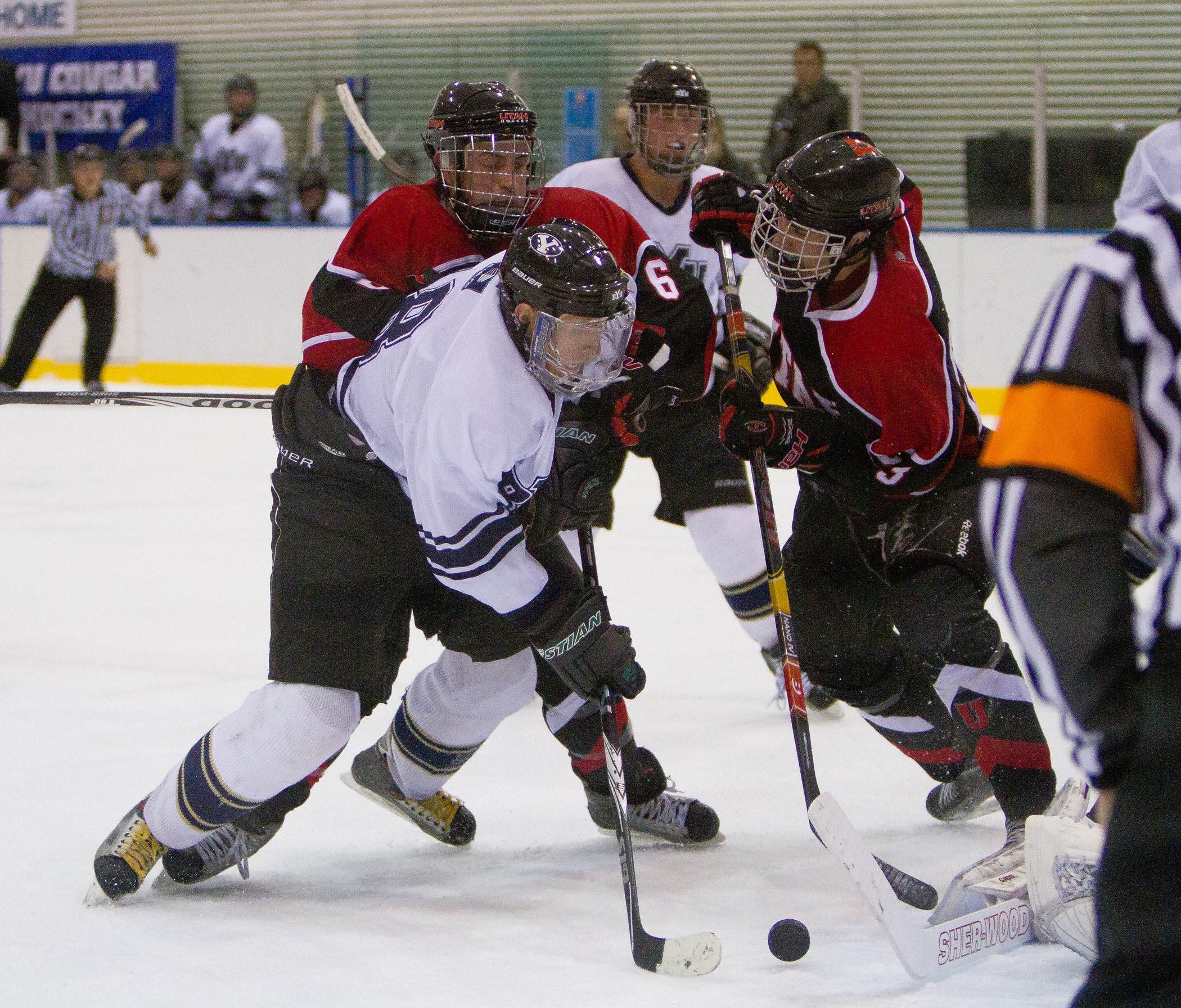 A BYU forward struggles for the puck against two Utah defenders in a game last season at Seven Peaks.