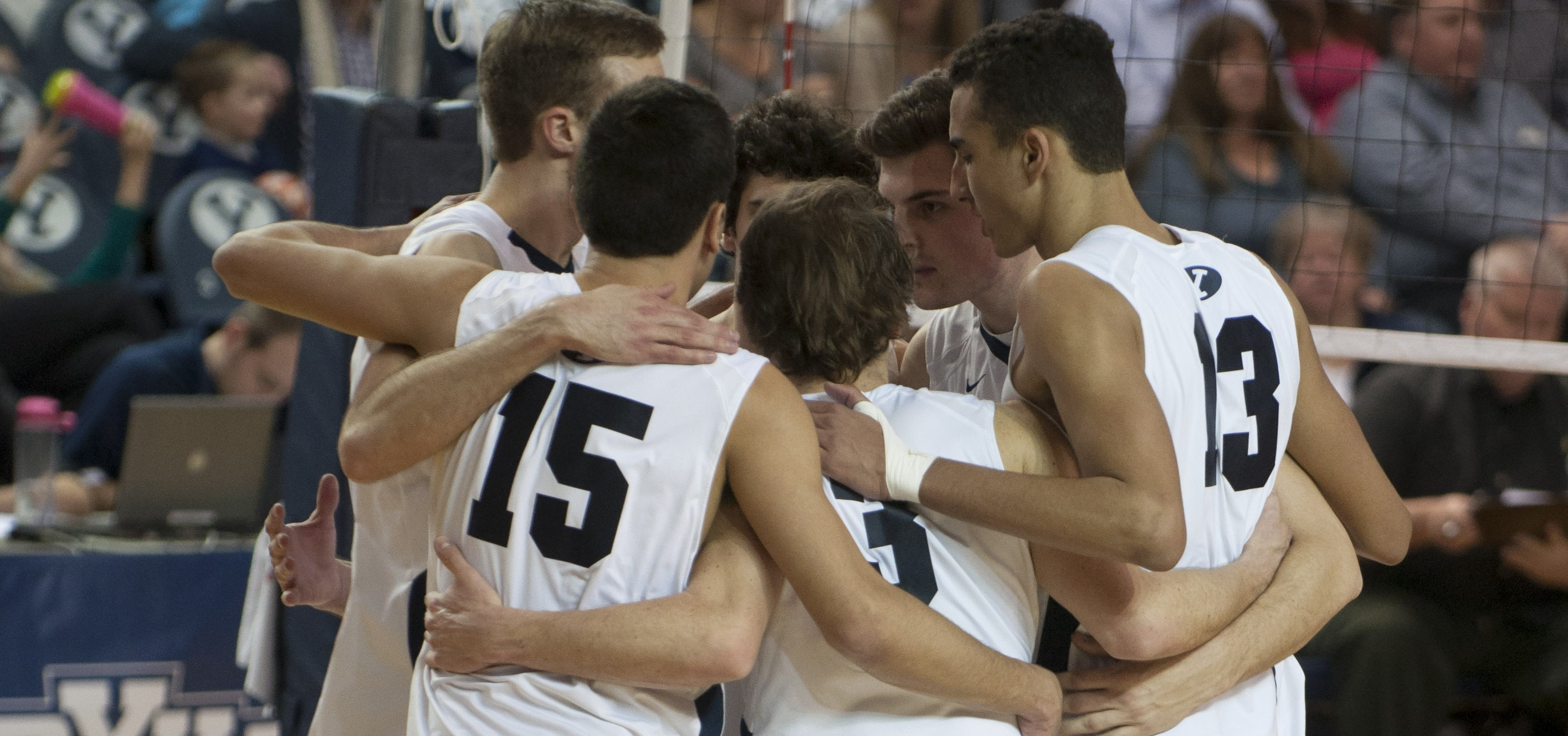 The BYU men's volleyball team huddles together after a point. (Photo by Whitnie Soelberg)