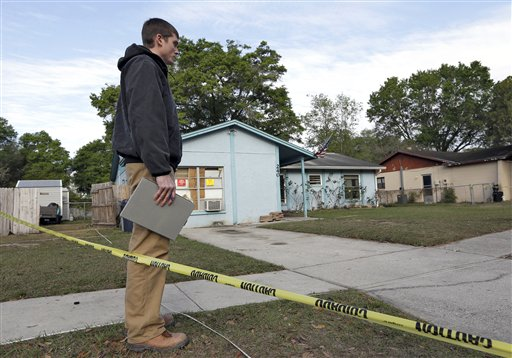 An engineer stands in front of a home where a sinkhole opened up on Friday. (AP Photo)