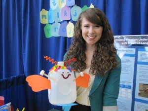 Becca Mansfield shows off her booth with a decorated milk jug used in her study. (Photo by Sara Bitterman)
