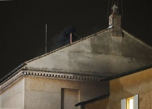 Black smoke emerges from the chimney on the roof of the Sistine Chapel, in St. Peter's Square at the Vatican, Tuesday, March 12, 2013. The black smoke indicates that the new pope has not been elected by the cardinals in conclave. (AP Photo/Michael Sohn)