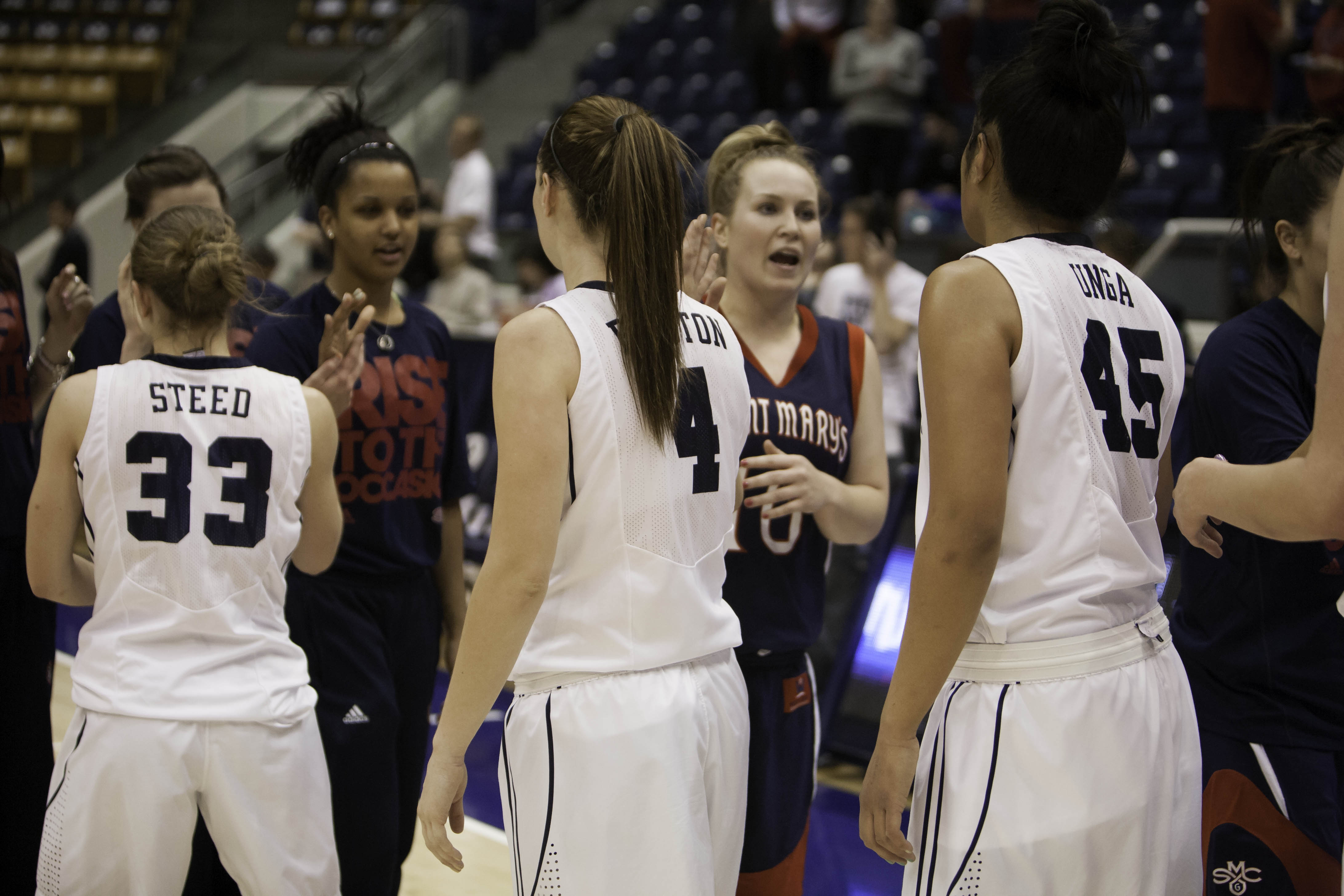 BYU players Haley Steed, Kim Beeston, and Keilani Unga congratulate St. Mary's players after the game on Wednesday. (Photo by Elliott Miller)