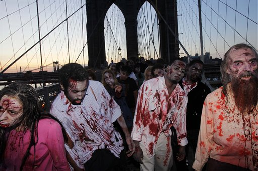 "Costumed actors, promoting the Halloween premiere of the AMC television series ""The Walking Dead"", shamble along the Brooklyn Bridge while posing for pictures in New York in October. (AP Photo)"