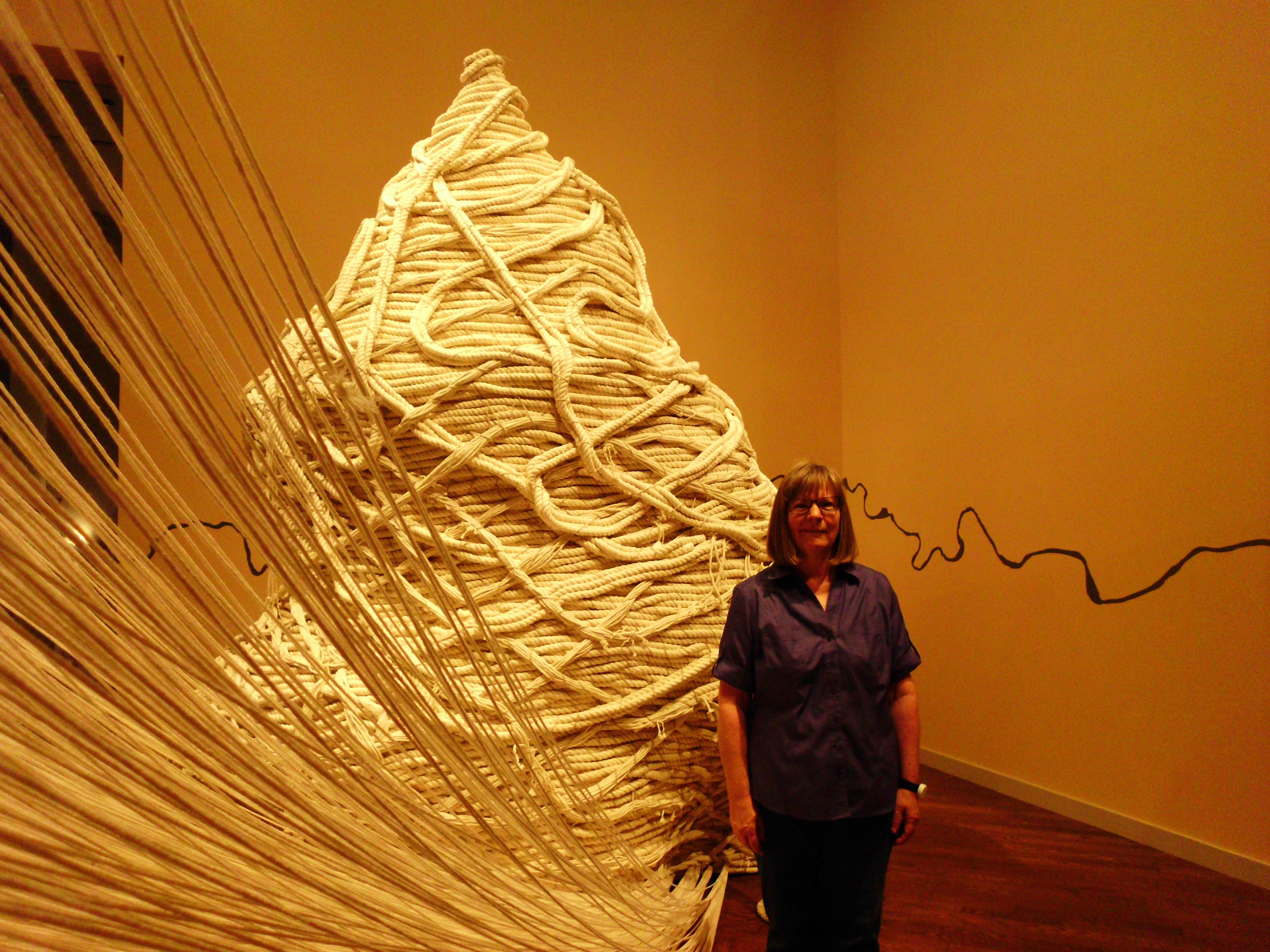 "Pam Bowman stands next to ""Becoming,"" the opening piece of the exhibit, which shows how small, everyday acts build up to create the whole of a person. (Photo by Mackenzie Brown)"