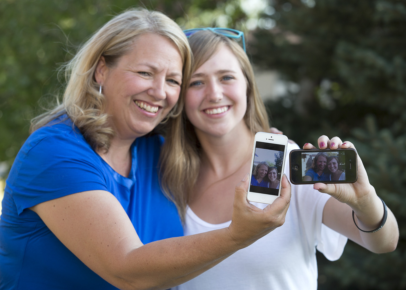 Syd and Brooke Jacques take photos of themselves on their smart phones. FOMO is (BYU Photo)