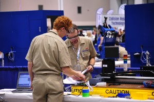 Photo Courtesy of UVU Marketing & Communications. UVU student Trezor Owens (left) competes in robotics and automation technology at the 49th annual SkillsUSA National Championships in Kansas City, Mo. He and teammate Jason Neely earned a gold medal in their category.