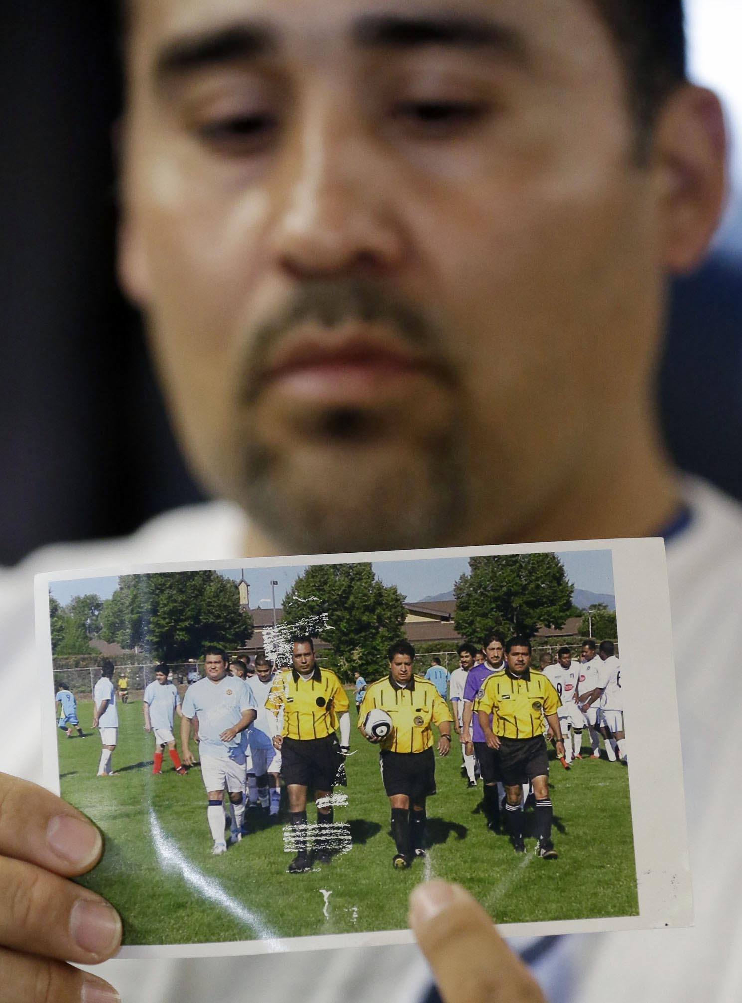 FILE - In this May 2, 2013 file photo, Jose Lopez points to a undated photo of Ricardo Portillo, center, his brother-in-law, following a news conference, at Intermountain Medical Center, in Murray, Utah. The attorney for a Utah teenager accused of killing a soccer referee with a single punch has acknowledged there is probable cause the teen committed the crime. The teenager's attorney, Monte Sleight, made the concession Friday, Aug. 2, 2013 in a private meeting with prosecutors and Juvenile Court Judge Kimberly Hornak, court records show. (AP Photo/Rick Bowmer, File)