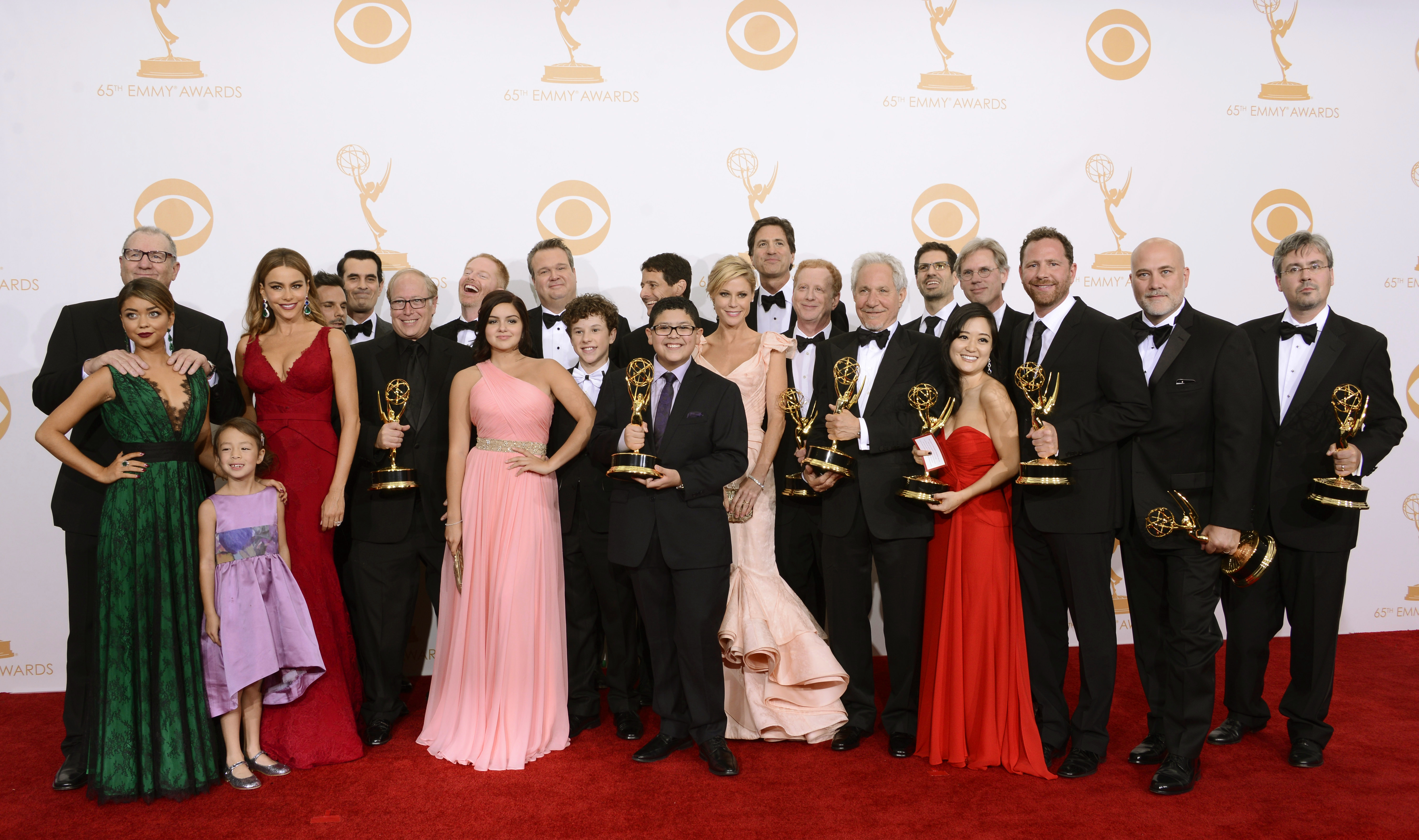 """Cast and crew from """"Modern Family"""" pose with their Emmy for outstanding comedy series backstage at the 65th Primetime Emmy Awards at Nokia Theatre on Sunday Sept. 22, 2013, in Los Angeles.  (Photo by Dan Steinberg/Invision/AP)"""