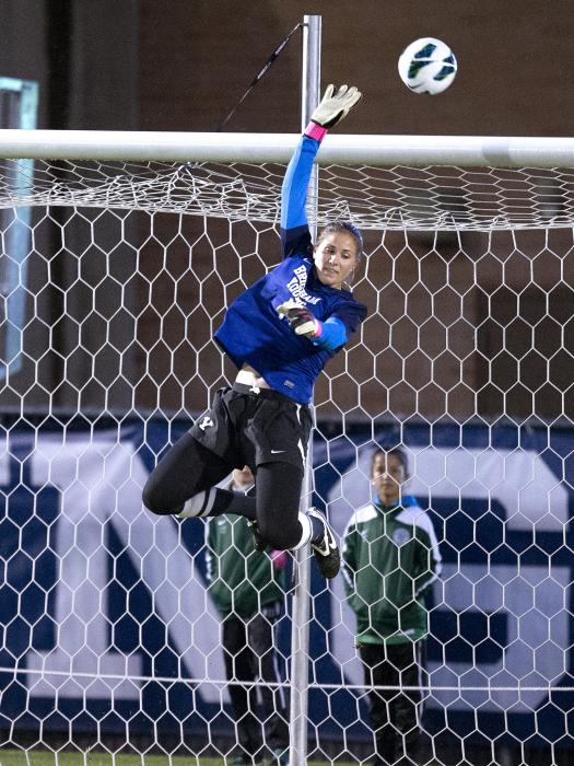 Erica Owens makes a leaping save during a BYU home game. Photo courtesy Jaren Wilkey/ BYU Photo