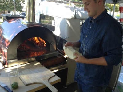 Matt Reschke, an advertising major at BYU, molds Italian-style dough into a pizza before placing it into the oven at the Provo Farmer's Market. Photo by Lucy Schouten.