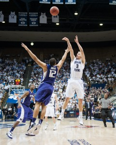 BYU guard Tyler Haws shoots over Washington defender Andrew Andrews during the 2012 NIT tournament. Photo by Sarah Hill