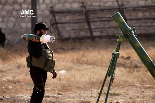 This Monday, Nov. 11, 2013 citizen journalism image provided by Aleppo Media Center AMC which has been authenticated based on its contents and other AP reporting, shows a Free Syrian Army fighter preparing to reload a mortar during an attack over Syrian government forces in Aleppo, Syria. Activists say clashes have flared up between Syrian troops and rebels on the southern outskirts of Damascus as part of a weeks-long government push to advance on opposition-held areas. (AP Photo/Aleppo Media Center AMC)