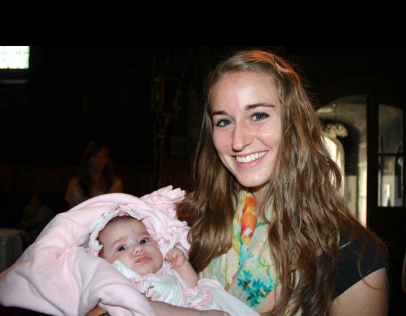 Ashleigh Cox holds a Romanian baby at an Orthodox baptism. Cox died Sunday, Feb. 9, after sustaining injuries from an avalanche Saturday, Feb. 8.