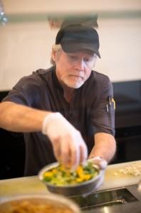 Owner Dorian Kidd prepares a salad at 180 Street Taco. (Photo by Sarah Hill.)