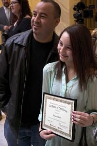 Azteca Valerio-Bedolla getting her photo taken with her award.