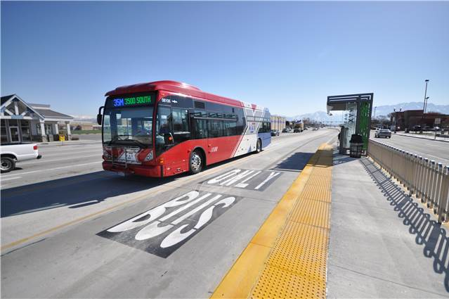 A Bus Rapid Transit vehicle pulls up to a stop on route, demonstrating the use of bus only lanes associated with BRT systems. Photo Courtesy of Utah Transit Authority