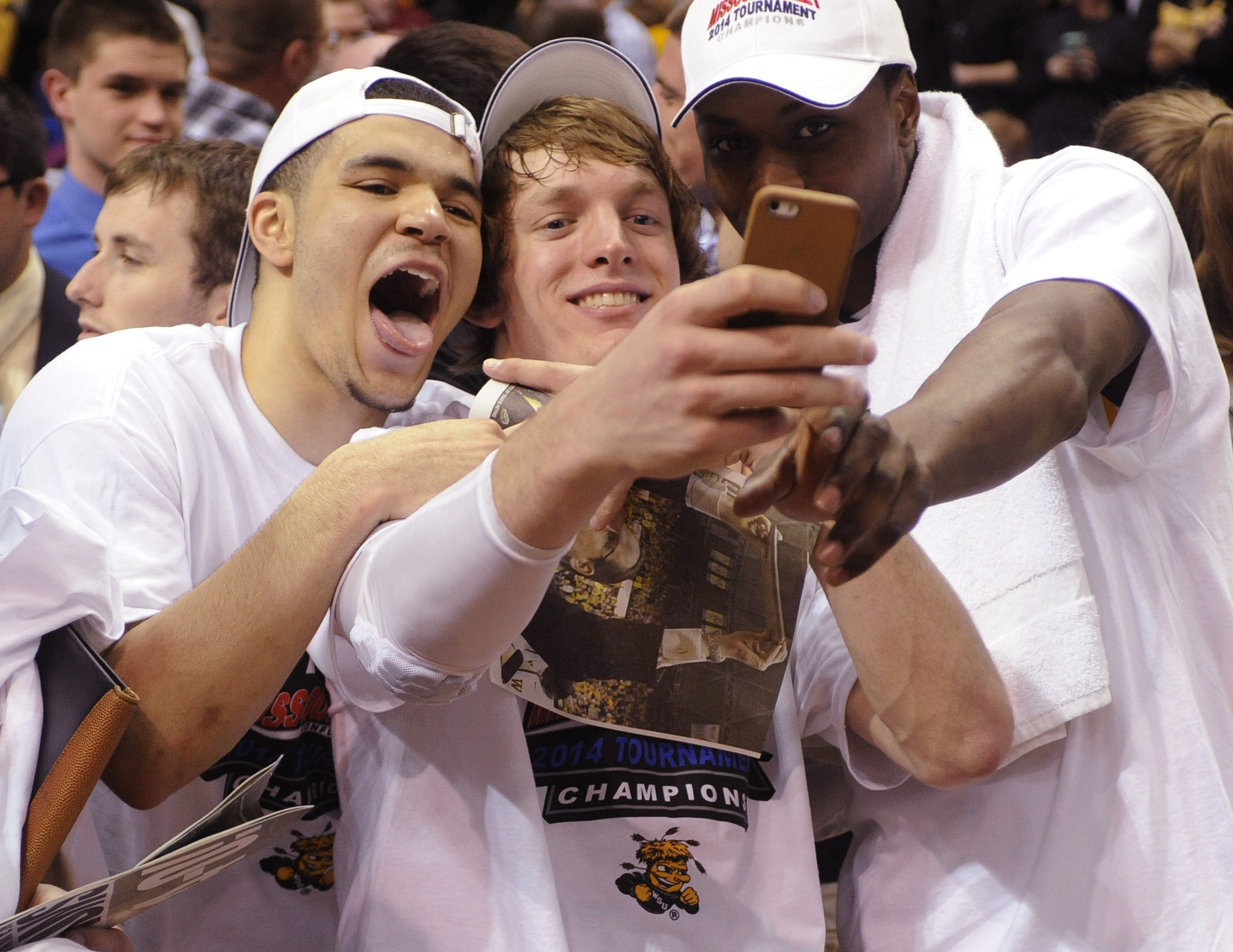 Wichita State's Ron Baker, center, takes a photo with Fred VanVleet, left, and Cleanthony Early, right, after their victory over Indiana State in the championship of the Missouri Valley Conference men's tournament March 9. A Cinderella team last year, the Shockers enter the NCAA tournament as a No. 1 seed this year. (AP Photo/Bill Boyce)