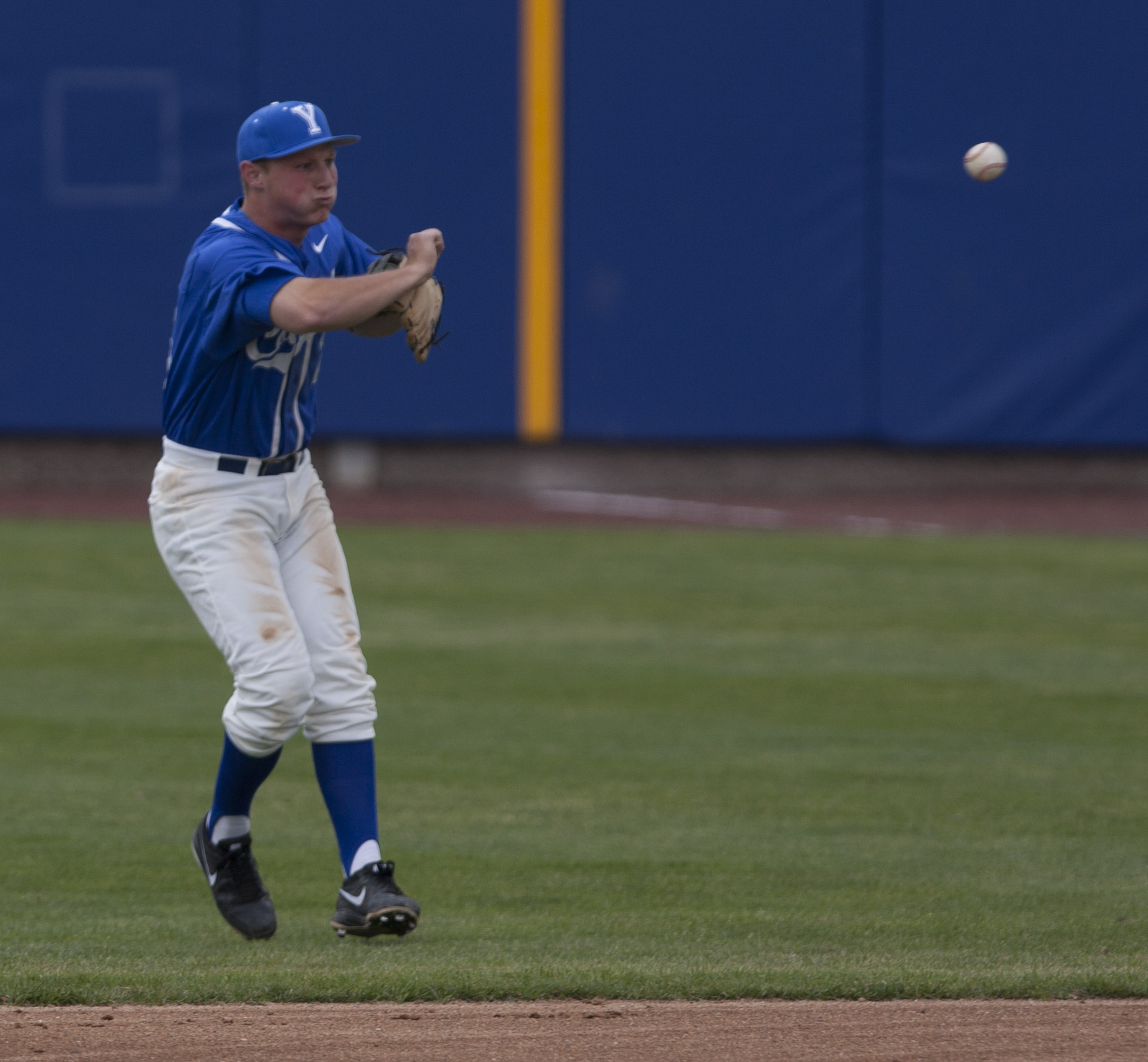 BYU shortstop Hayden Nielsen jumps and throws to first base for an out. Photo by Natalie Stoker