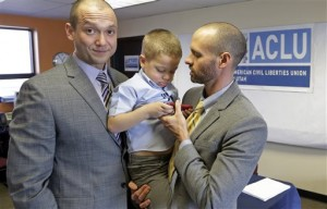 plaintiffs Matthew Barraza, left, looks on as his husband Tony Milner, right, holds their son Jesse, 4, following a news conference in Salt Lake City. Photo by Associated Press.