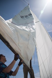 Jared Bishop straightens out the sail of a sailboat with assistance from Lloyd Grubham. Photo by Ari Davis