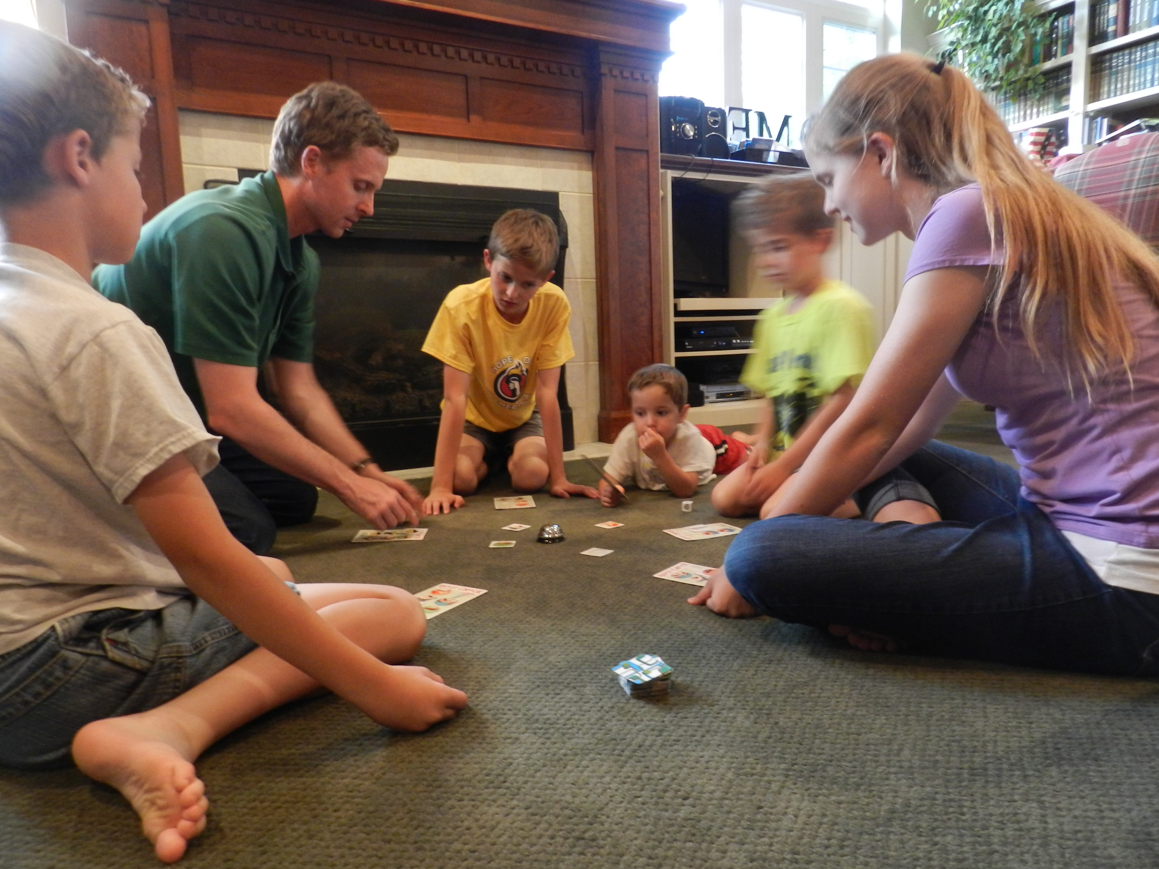 """Myles Christensen, mechanical engineering professor, loves spending time with his family, especially playing games such as """"Order's Up,"""" pictured above. This is a game he invented where players rush to serve a table of hungry customers. (Jeffrey Allen)"""