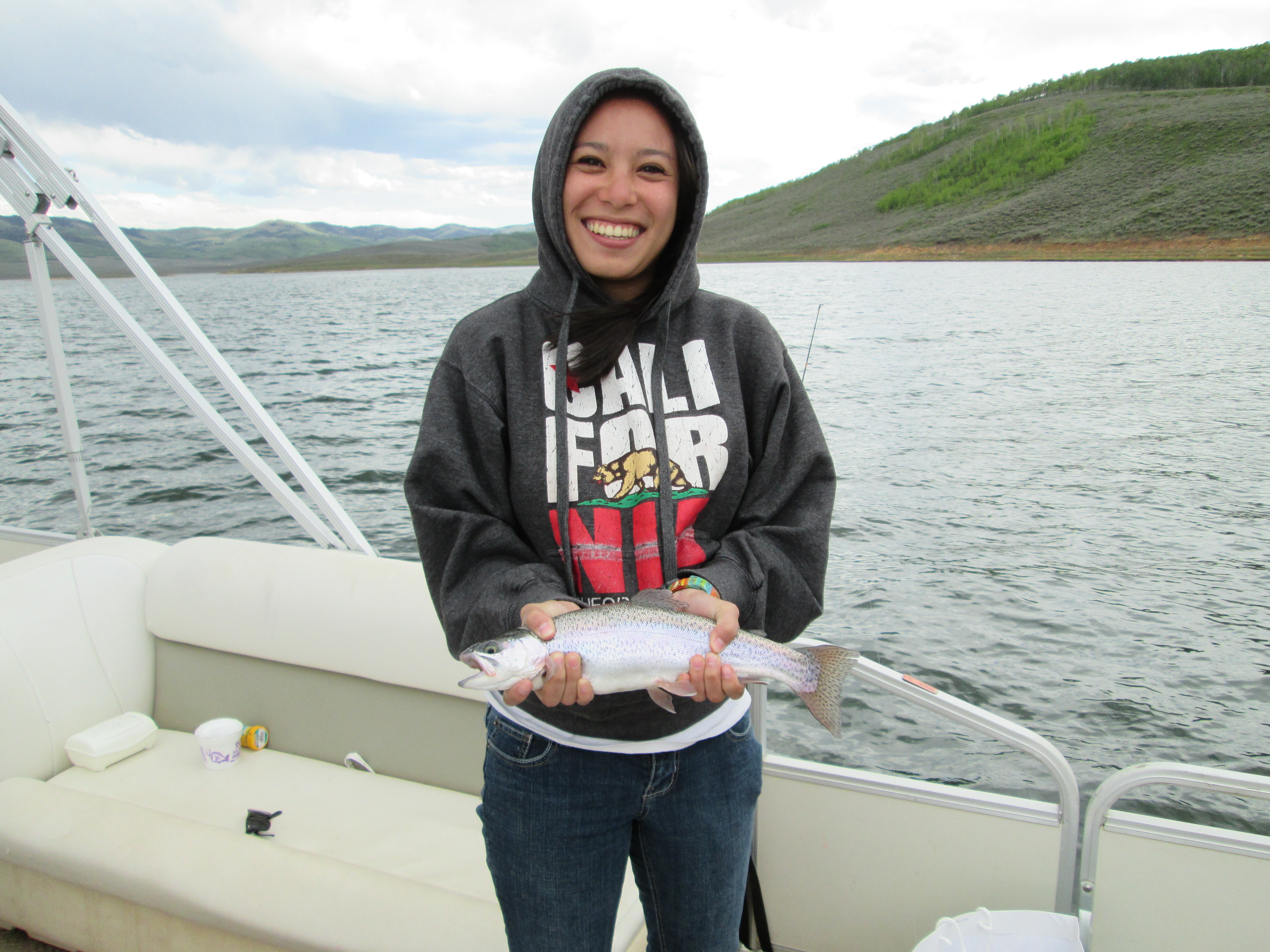 Ashley Urquhart holds a rainbow trout she caught at Strawberry Reservoir in May. (Photo by Tom Urquhart.)