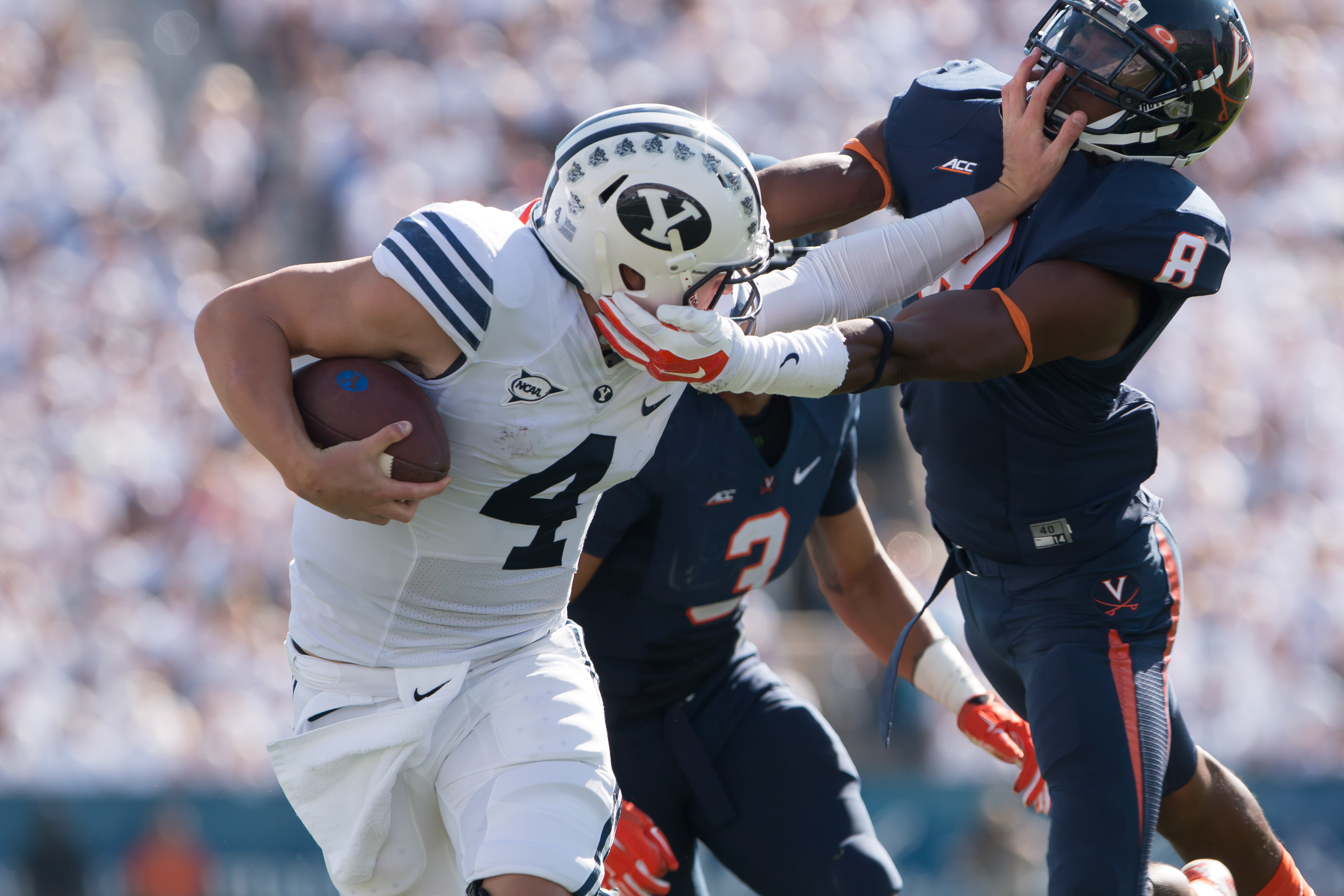 Taysom Hill runs with the ball, fighting through Virginia opposition to score a touchdown. (Maddi Dayton)