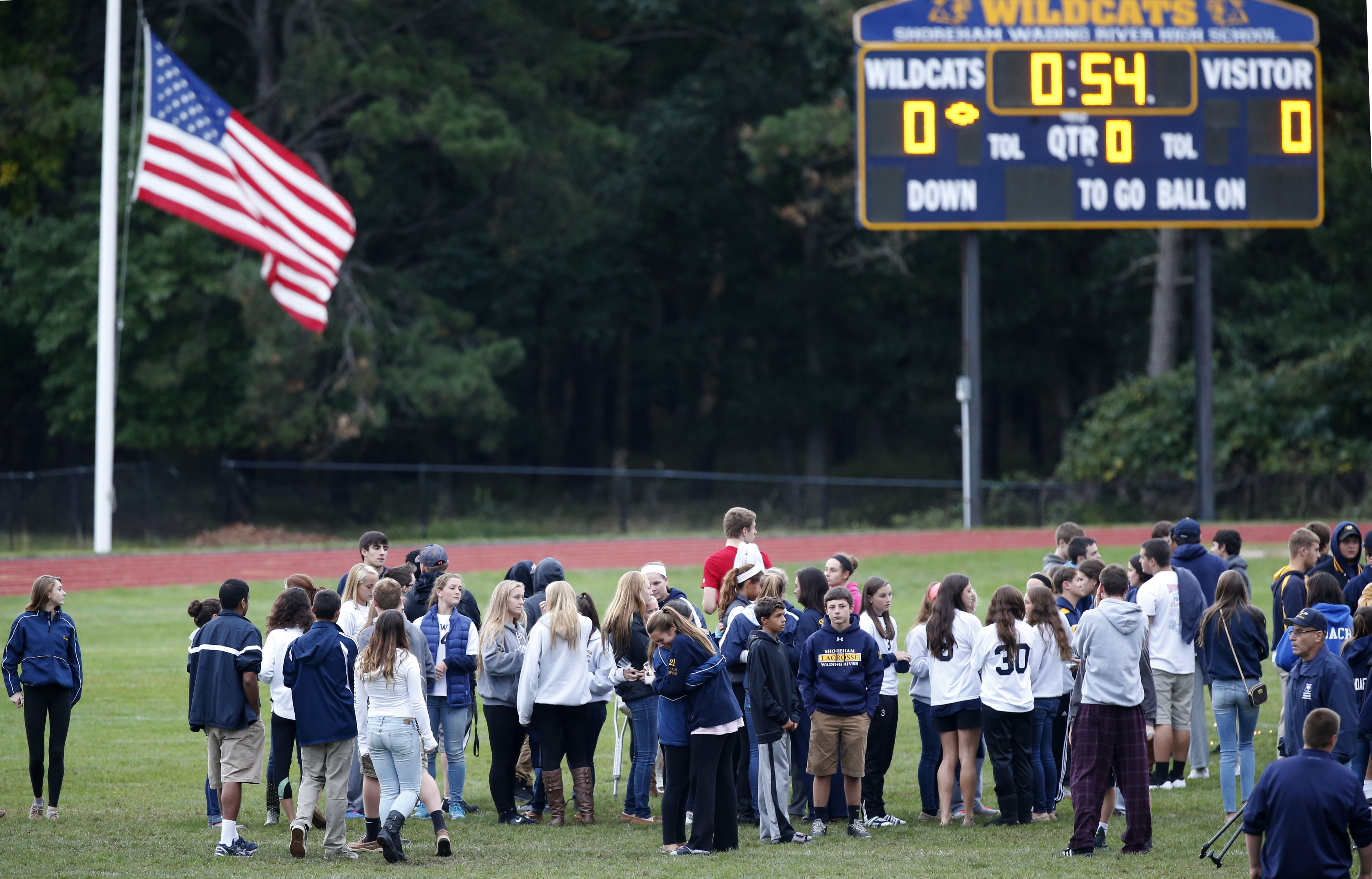 People walk on the football field at Shoreham Wading River High School in Shoreham, N.Y., Thursday, Oct. 2, 2014, after a vigil for 16-year-old varsity football player Tom Cutinella, who died Wednesday night after a fatal football collision at an away game . (AP Photo/Kathy Willens)