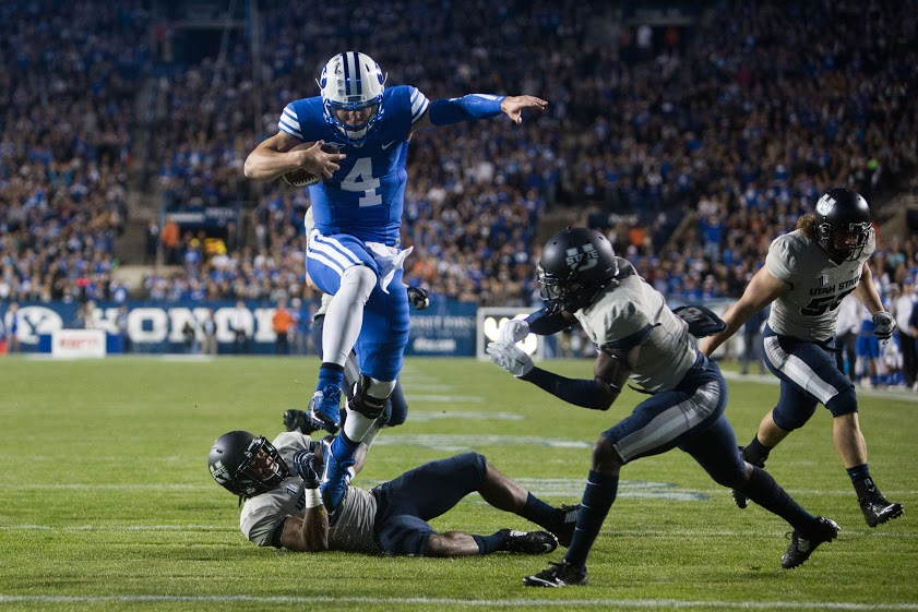 Taysom Hill leaps over Utah State players into the end zone during last season's game. (Elliott Miller)