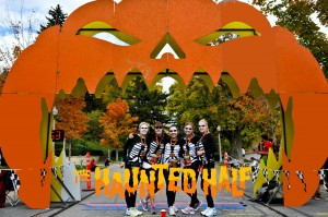 Participants dressed up as skeletons pose at the finish line of The Haunted Half with their finishers medals. (Photo by Lucid Images)