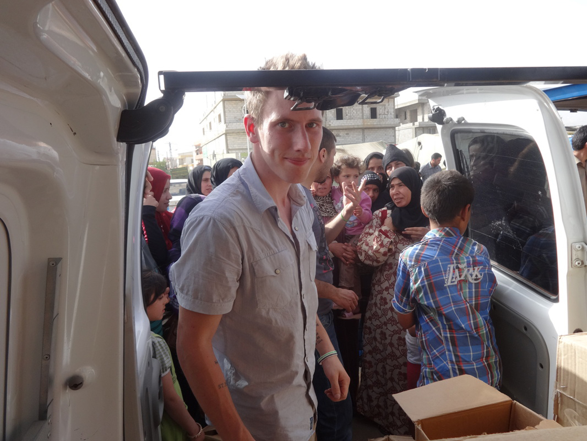 This undated photo provided by the Kassig Family shows Peter Kassig delivering supplies for Syrian refugees. A new graphic video purportedly produced by Islamic State militants in Syria released Sunday Nov. 16, 2014 claims U.S. aid worker Kassig was beheaded. (AP Photo/Courtesy Kassig Family)