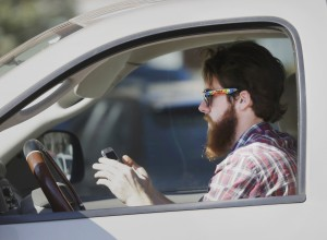 A man uses his cell phone as he drives through traffic in Dallas. In a new survey, 98 percent of motorists who own cellphones and text regularly were aware of the dangers, yet three-quarters of them admit to texting while driving, despite laws against it in some states. Two-thirds said they have read text messages while stopped at a red light or stop sign, while more than a quarter said they have sent texts while driving. (AP Photo/LM Otero)