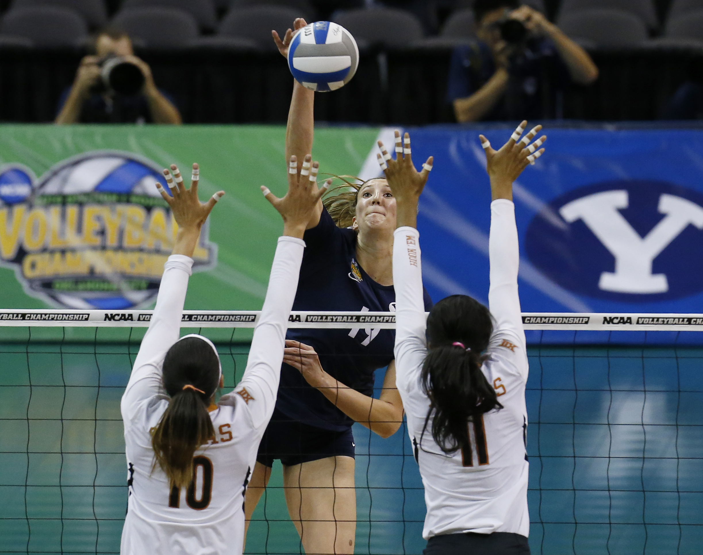 BYU's Jennifer Hamson (19) hits a kill over Texas's Haley Eckerman (10) and Chiaka Ogbogu (11) during an NCAA college volleyball tournament semifinal in Oklahoma City, Thursday, Dec. 18, 2014. (AP Photo/Sue Ogrocki)