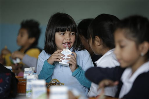 Hazel Loarca, 7, drinks her milk in the cafeteria area at Kingsley Elementary School, Tuesday, Jan. 13, 2015, in Los Angeles. Many of the students at the school in a low-income neighborhood of Los Angeles eat breakfast and lunch provided by the school. For the nearly 100 enrolled in the afterschool program, another meal is served: supper. The nation's second largest school district is doubling the number of students served dinner, with an eye toward eventually offering it at every school. (AP Photo/Jae C. Hong)