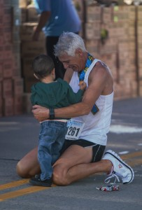 A runner is greeted by family after he crosses the finish line. Over 1,700 runner and volunteers were involved in this year 2015 Provo Half Marathon. (Maddi Dayton)