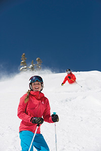 Good friends making turns on a gorgeous bluebird day. Smiles don't cease despite the below-average snowfall this season.  (Dan Campbell/Ski Utah)