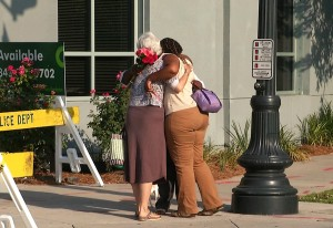 In this image taken from video on Thursday, June 18, 2015, Martha Watson, left, and Tarsha Moseley embrace at a makeshift memorial near Emanuel AME Church in Charleston, S.C. A white man opened fire during a prayer meeting inside the historic black church Wednesday night, killing several people. The shooter remained at large Thursday morning. (AP Photo/Alex Sanz)