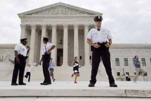 Interns run behind a line of security outside of the Supreme Court in Washington, Friday June 26, 2015, to reveal the court's decision declaring that same-sex couples have a right to marry anywhere in the US. (AP Photo/Jacquelyn Martin)