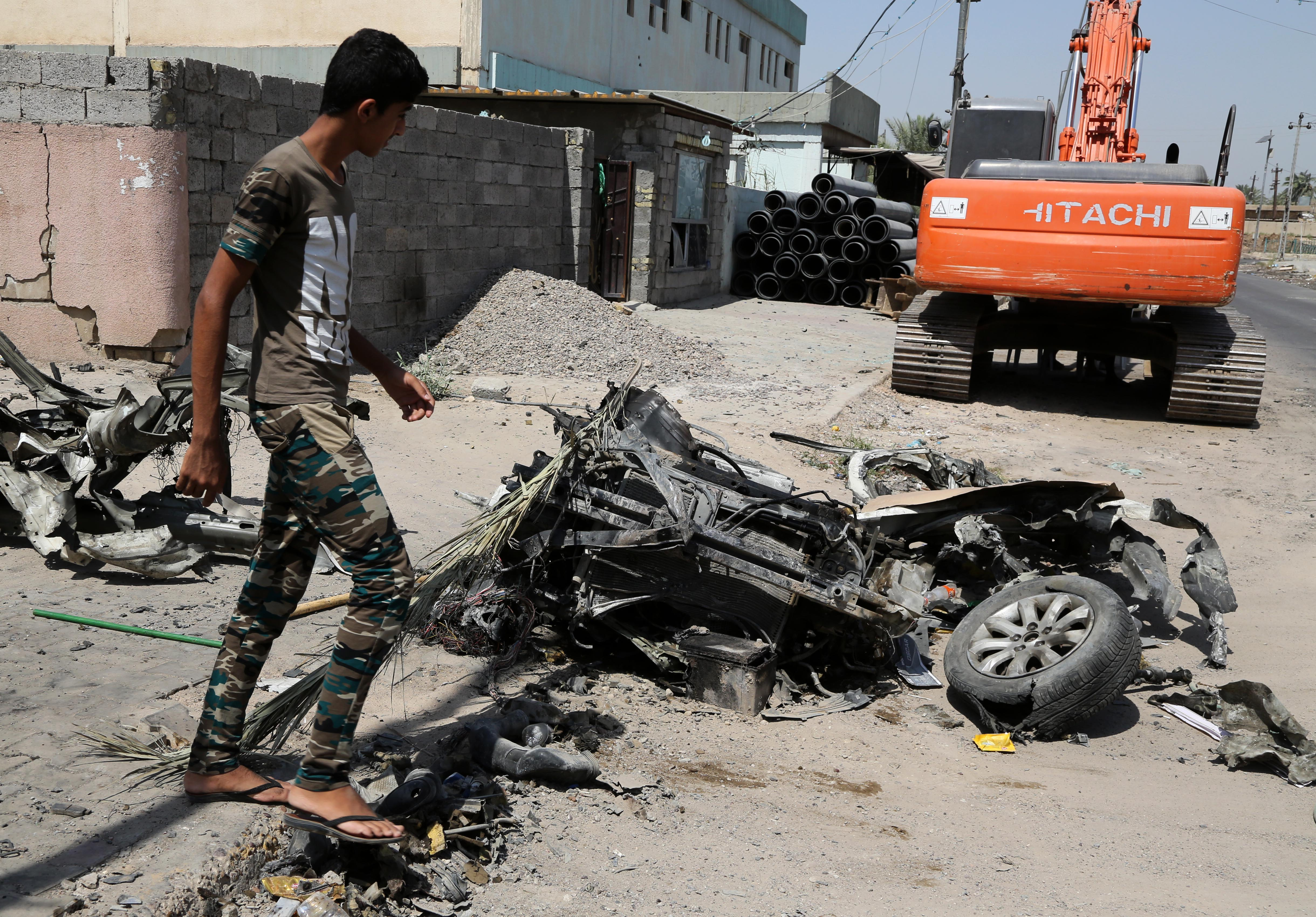 A man inspects the scene of an explosion in a busy commercial area in Baghdad, Iraq Monday, July 13, 2015. A string of car bombs and explosive belts attacks across Baghdad killed and wounded dozens of people on Sunday, Iraqi officials said. (AP Photo/Karim Kadim)