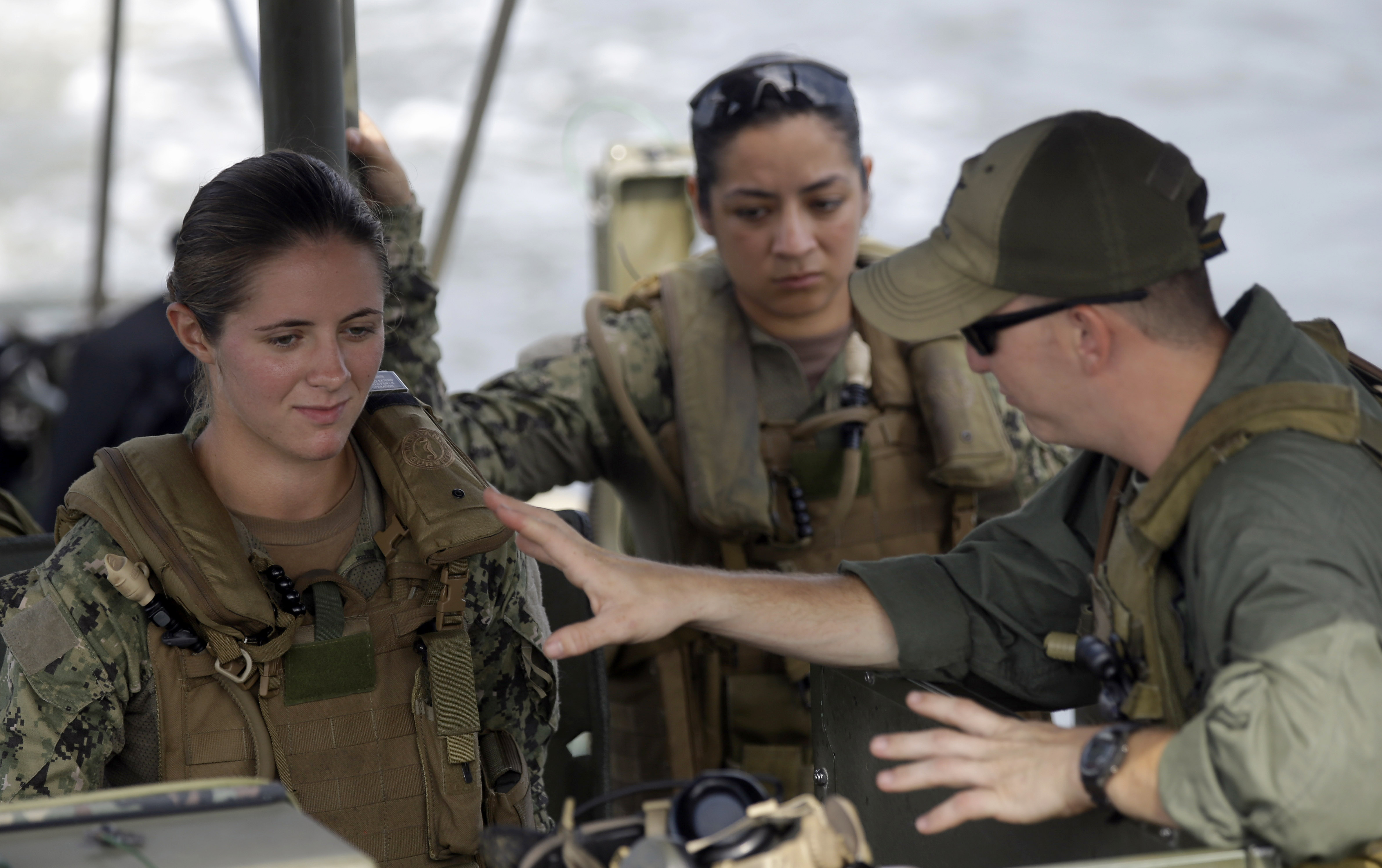 RETRANSMISSION TO REMOVE THE REFERENCE TO THE ARMY RANGERS. THESE WOMEN ARE NOT TRAINING IN THE RANGERS PROGRAM - FILE - In this Aug. 13, 2013 file photo, U.S. Navy Master-at-Arms Third Class Danielle Hinchliff, left, and Master-at-Arms Third Class Anna Schnatzmeyer, center, participate in a U.S. Navy Riverine Crewman Course under instructor Boatswain's Mate Second Class Christopher Johnson, right, on a Riverine Assault Boat at Camp Lejeune, N.C. The U.S. military services appear poised to allow women to serve in most, if not all, front-line jobs, including as special operations forces, according to several senior officials familiar with the discussions. (AP Photo/Gerry Broome, File)