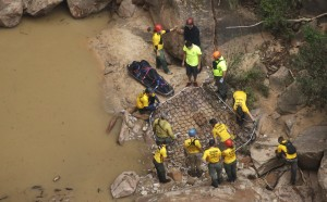 Search and rescue team members place a litter in a net for helicopter transport after finding a body in Pine Creek on Wednesday, Sept. 16, 2015, in Zion National Park, near Springdale, Utah. Authorities are searching for other hikers killed in flash flooding that swept through a narrow canyon at Utah's Zion National Park. (AP Photo/Rick Bowmer)