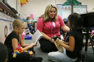 In this Sept. 10, 2015, photo, Tia Martin, center, works with Izabel Martinez, left, and Ashlyn Dowding in a third-grade class at Ulis Elementary School in Henderson, Nev. (Associated Press)