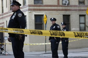 Police officers stand guard near an apartment building in the Bronx borough of New York, Thursday, Oct. 15, 2015. A 6-month-old girl died Thursday after being tossed from the window of an apartment building, witnesses and police said, the third child killed that way in the city in three months. (AP Photo/Mary Altaffer)