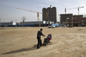 In this Monday, March 17, 2014, file photo, a man pushes a baby buggy near a construction site of a residential real estate project in a village on the outskirts of Beijing. China's ruling Communist Party announced Thursday, Oct. 29, 2015, that it will abolish the country's decades-old one-child policy and allow all couples to have two children, removing remaining restrictions that limited many urban couples to only one, the official Xinhua News Agency said. Associated Press