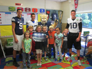Mitch Matthews and Jordan Leslie accompany Cosmo to an elementary school. Cosmo makes frequent appearances to elementary schools during the week. (BYU Athletic Marketing)