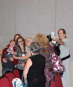Attendees take selfies with the Compassion Games torch. All participants in the 2015 Parliament of World's Religions received the handout in their bags. (Kjersten Johnson)
